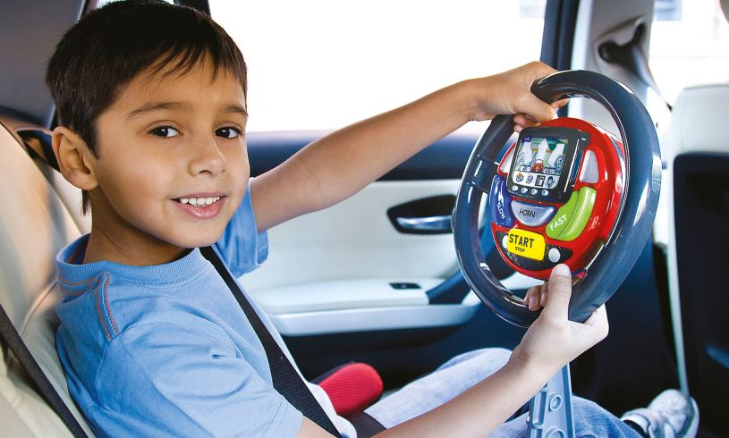 young boy with fake steering wheel