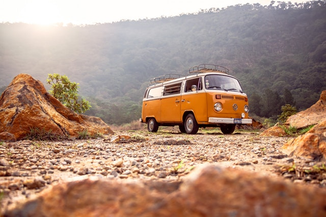 orange campervan parked in a rubbly, hilly area