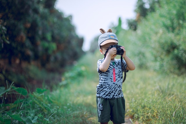 young child with a digital camera in a field