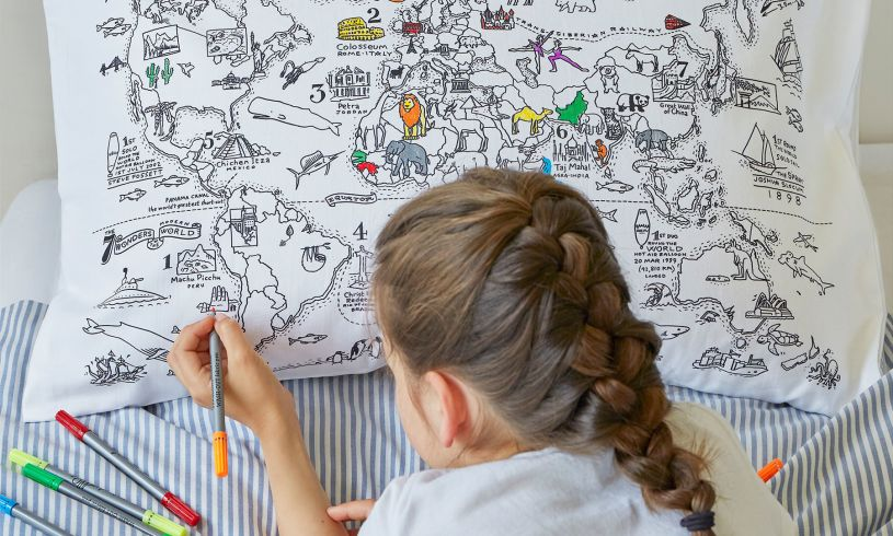 young girl drawing on the world map pillowcase