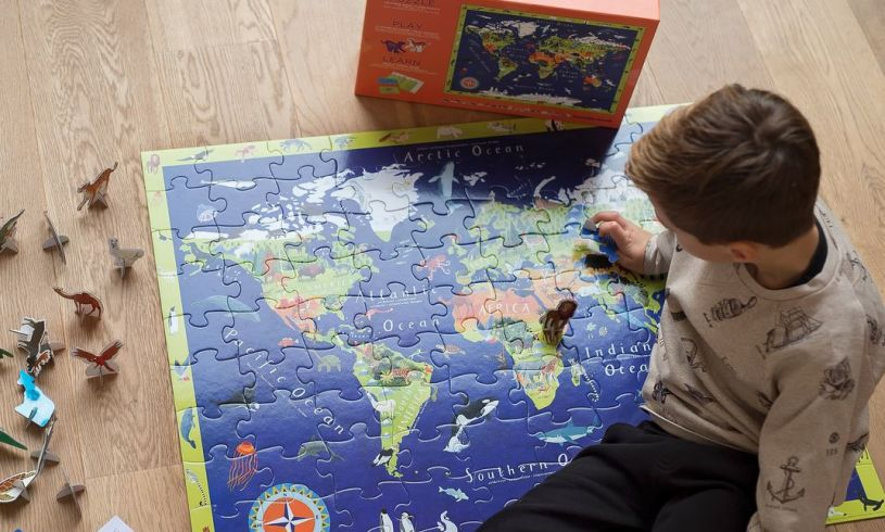 a young boy completing the Discover The World puzzle