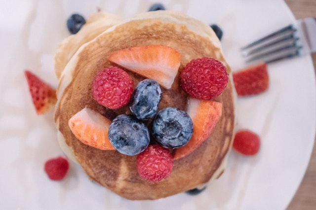 a stack of pancakes with blueberries, raspberries, and strawberries