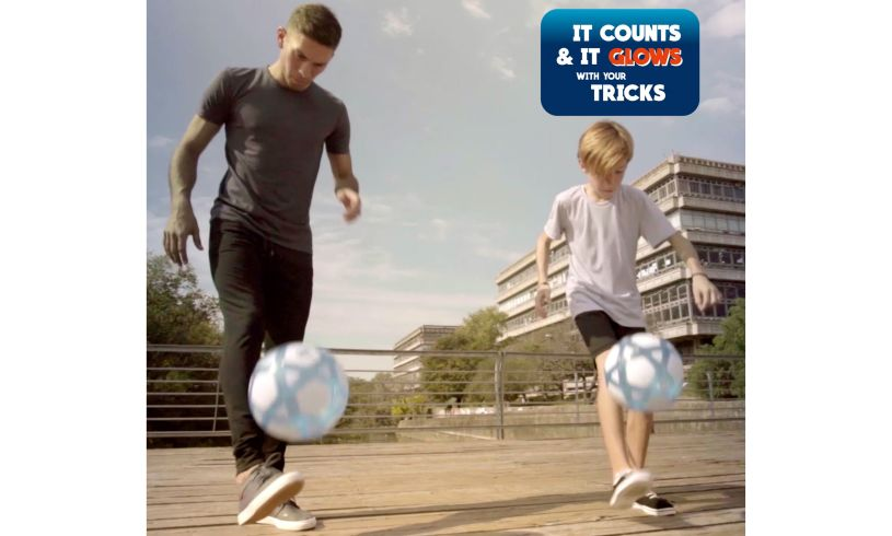 a man and a younger boy both doing keepy-uppys with the smart ball