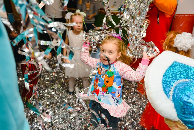 young girl playing in confetti