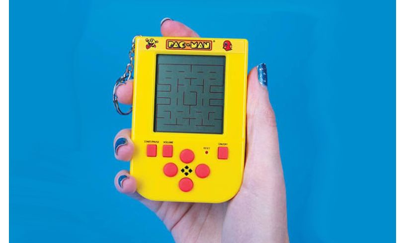 a hand holding the pac-man handheld game